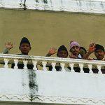 Children waving from balcony
